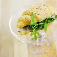Сендвич-круассан с беконом и рукколой Фото