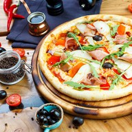 Пицца с пармским окороком и грушей Фото