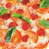 Пицца с сыром моцарелла и колбасой Фото