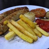 Колбаски гриль с овощами, картофелем фри Фото