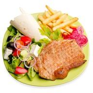 Тарелка со стейком из свинины Фото